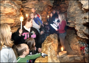 Members of the River City Revue, from Hannibal High School, Erica Graham, Hannah Adkison, and Duane Jones, led by Director Kate Valuck, sing Christmas carols at stops along the 45 minute tour through Mark Twain Cave Sunday. (H-W Photo/Michael Kipley)