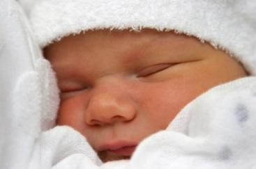 A newborn baby snuggling into white linen
