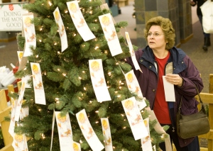 NICK WOLCOTT/CHRONICLE Debbie Johnson picks out gift requests from the Salvation Army's Angel Giving Tree at the Gallatin Valley Mall on Thursday.